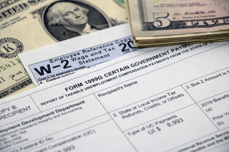 Closeup of a Form 1099G Certain Government Payments for unemployment benefits atop a W2 form and dollar bill, with stack of $5 bills.