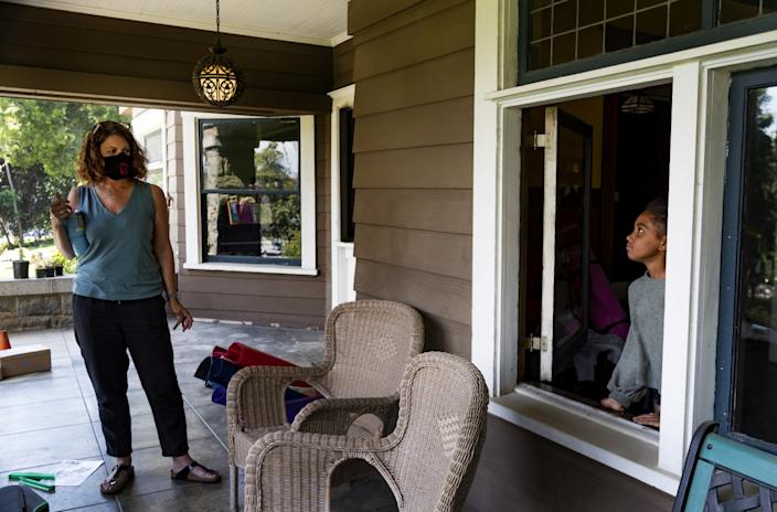"Former third-grade teacher Kristen Bristow listens to her daughter Andie, 6, on the porch of their Craftsman-style home. <span class=""copyright"">(Gina Ferazzi / Los Angeles Times)</span>"