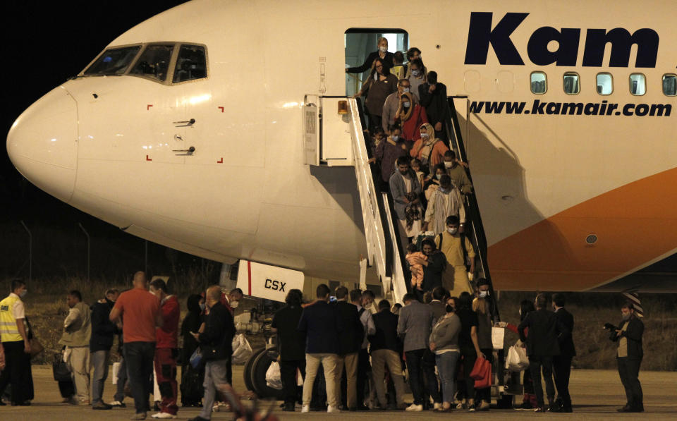 Afghan evacuees disembark a plane after landing at Skopje International Airport, North Macedonia, late Monday, Aug. 30, 2021. A first group of 149 Afghan evacuees landed late Monday in North Macedonia, where they will stay for a few months pending resettlement elsewhere. (AP Photo/Boris Grdanoski)