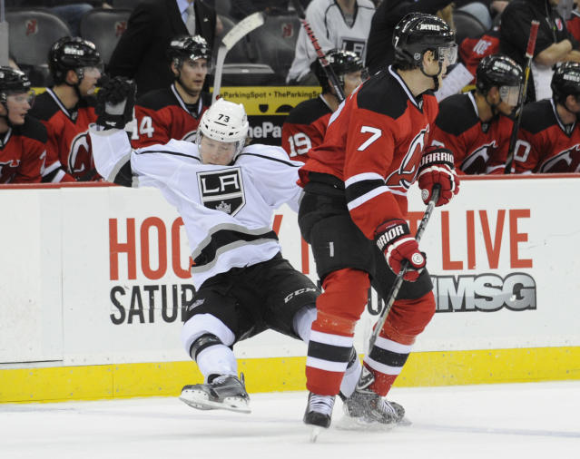 Los Angeles Kings' Tyler Toffoli, left, loses his balance as he collides with New Jersey Devils' Mark Fayne during the first period of an NHL hockey game Friday, Nov. 15, 2013, in Newark, N.J. (AP Photo/Bill Kostroun)