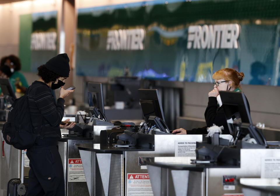 A passenger, left, checks in with an agent at the ticketing counter for Frontier Airlines at Denver International Airport, Sunday, May 3, 2020, in Denver during the coronavirus outbreak. (AP Photo/David Zalubowski)