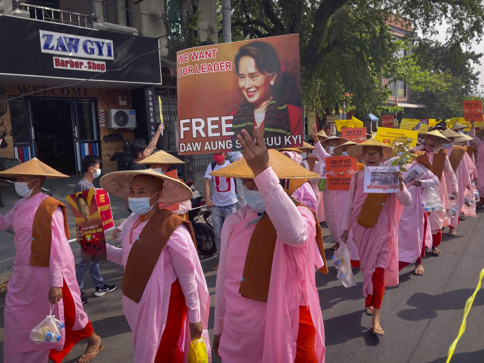 Buddhist nuns display images of deposed Myanmar leader Aung San Suu Kyi during a street march in Mandalay, Myanmar, Friday, Feb. 26, 2021. Tensions escalated Thursday on the streets of Yangon, Myanmar's biggest city, as supporters of Myanmar's junta attacked people protesting the military government that took power in a coup, using slingshots, iron rods and knives to injure several of the demonstrators. (AP Photo)