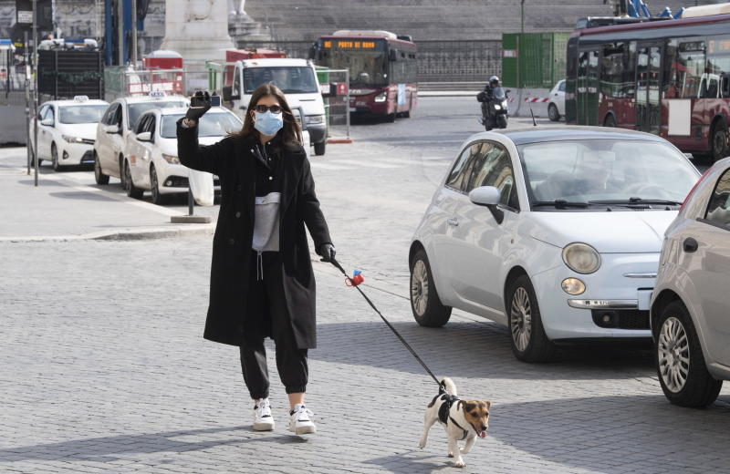 A woman wearing a face mask and gloves walks her dog in Rome, Italy.