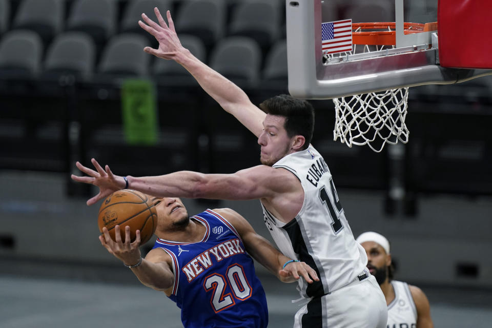 New York Knicks forward Kevin Knox II (20) is defended by San Antonio Spurs forward Drew Eubanks (14) as he drives to the basket during the second half of an NBA basketball game in San Antonio, Tuesday, March 2, 2021. (AP Photo/Eric Gay)