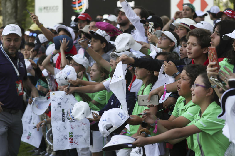 Fans callout to Rory McIlroy of Northern Ireland for an autograph at the ninth green during a practice round for the WGC-Mexico Championship golf tournament, at the Chapultepec Golf Club in Mexico City, Wednesday, Feb. 19, 2020. (AP Photo/Fernando Llano)