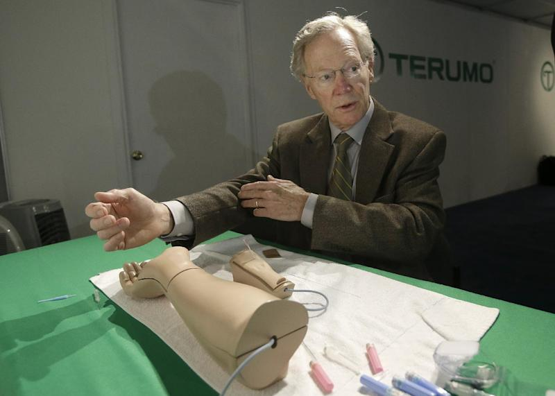 In this Monday, March 11, 2013 photo, Atlanta cardiologist Dr. Spencer King demonstrates how doctors can open blocked heart arteries by going through an arm, using a model, at the American College of Cardiology conference in San Francisco. The original catheter-based treatment, balloon angioplasty, is still used hundreds of thousands of times each year in the U.S. alone. A Japanese company, Terumo Corp., is one of the leaders of a new way to do it that is easier on patients - through a catheter in the arm rather than the groin. (AP Photo/Jeff Chiu)