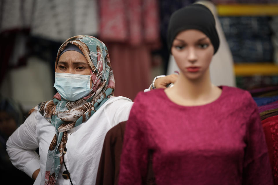 A Muslim vendor wearing protective mask waiting for customers at a Ramadan bazaar, amid the outbreak of the coronavirus disease (COVID-19) in Kuala Lumpur, Malaysia, Monday, April 19, 2021. (AP Photo/Vincent Thian)