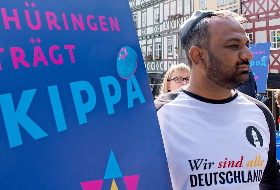 Muslim Sulaman Malik of the Ahmadiyya community wears the Jewish kippah during a demonstration against antisemitism in Germany in Erfurt, Germany, Wednesday, April 25, 2018. The words at the T-shirt reads: 'We are Germany'.  (AP Photo/Jens Meyer)