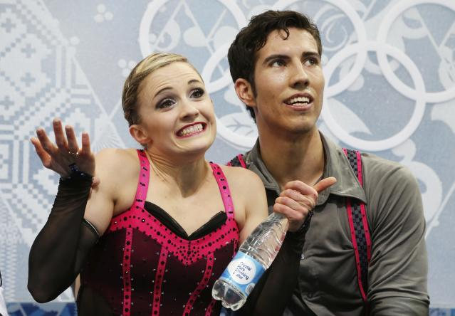 """Canada's Paige Lawrence and Rudi Swiegers react in the """"kiss and cry"""" area during the Figure Skating Pairs Short Program at the Sochi 2014 Winter Olympics, February 11, 2014. REUTERS/Lucy Nicholson (RUSSIA - Tags: OLYMPICS SPORT FIGURE SKATING)"""