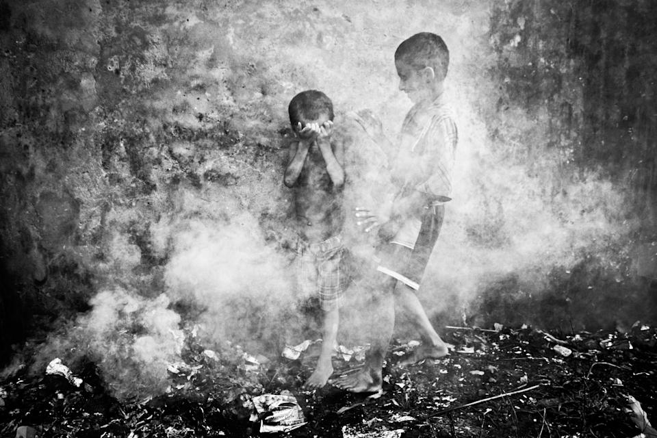 """Two homeless street children were playing in the smoke created from burnt straws at Chittagong, Bangladesh. Suddenly dense smoke covered them and they were trying to protect themselves and escape. (Kazi Riasat Alve, Bangladesh, Shortlist, Split Second, Open Competition 2013 Sony World Photography Awards) <br> <br> <a href=""""http://worldphoto.org/about-the-sony-world-photography-awards/"""" rel=""""nofollow noopener"""" target=""""_blank"""" data-ylk=""""slk:Click here to see the full shortlist at World Photography Organisation"""" class=""""link rapid-noclick-resp"""">Click here to see the full shortlist at World Photography Organisation</a>"""