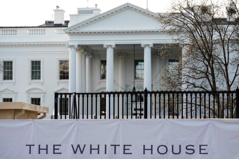 The new fence surrounding the White House is seen behind a screen in Washington