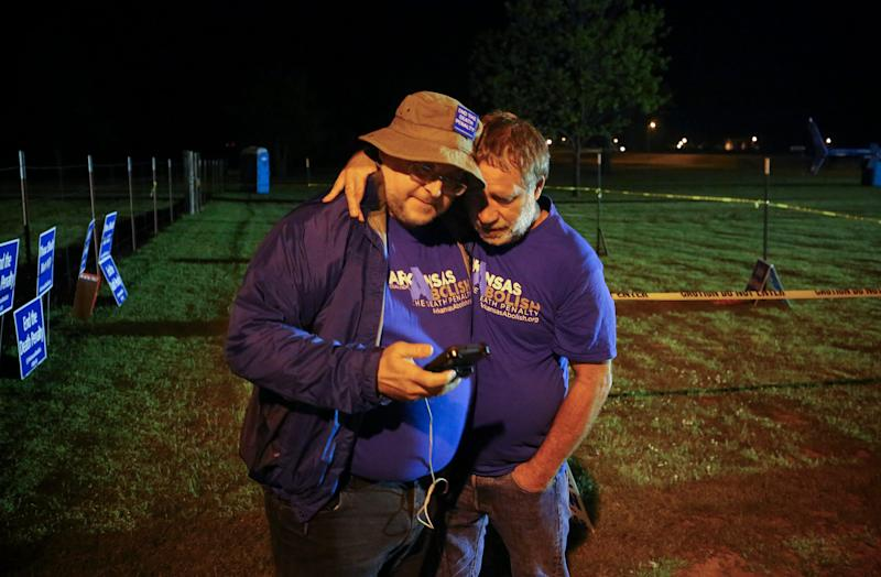 "Anti-death penalty supporter Randy Gardner, right, embraces Abraham Bonowitz, left, after they read on his phone the 11:45 p.m., decision to halt the execution in their taped off ""protest corral""  - Credit: AP"