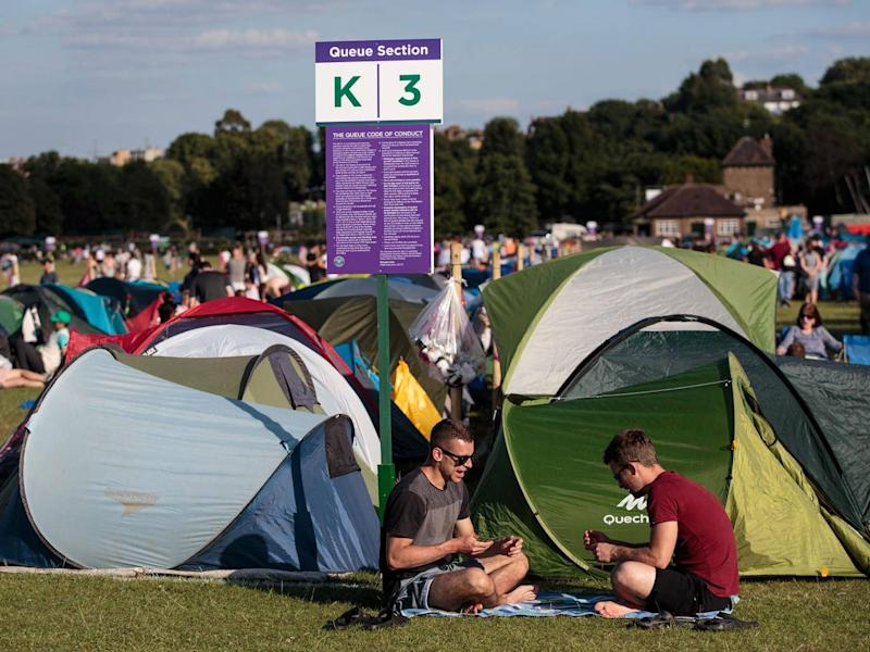 Wimbledon fans patiently wait on the morning of the opening day (Getty)