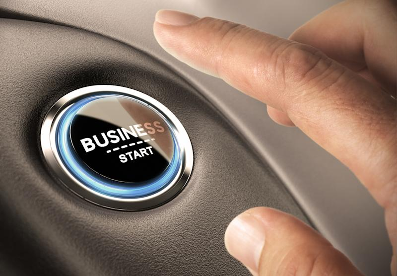 A person with his or her finger above a button labeled BUSINESS START.