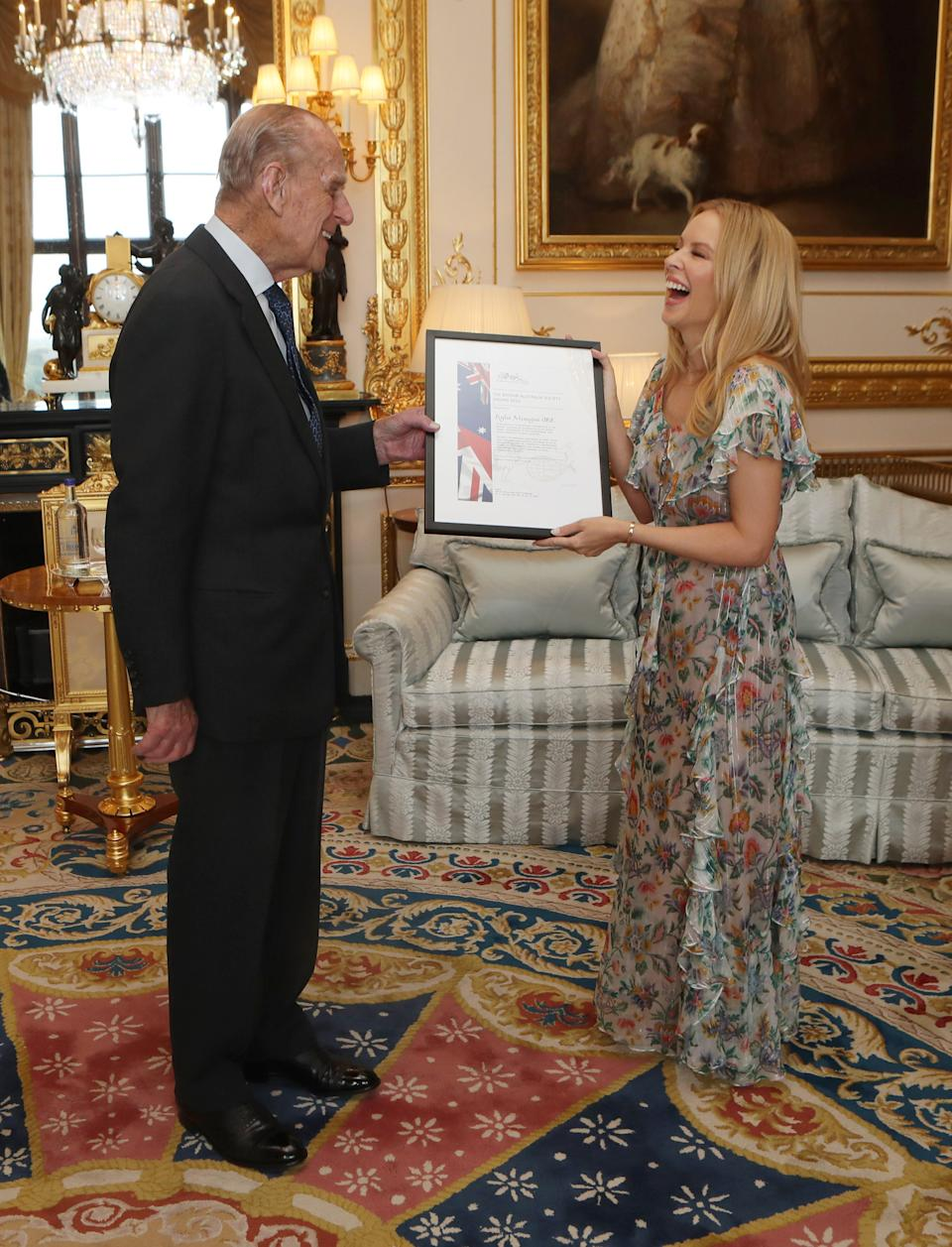 Prince Philip laughs as he presents Kylie Minogue with the Britain-Australia Society Award for 2016