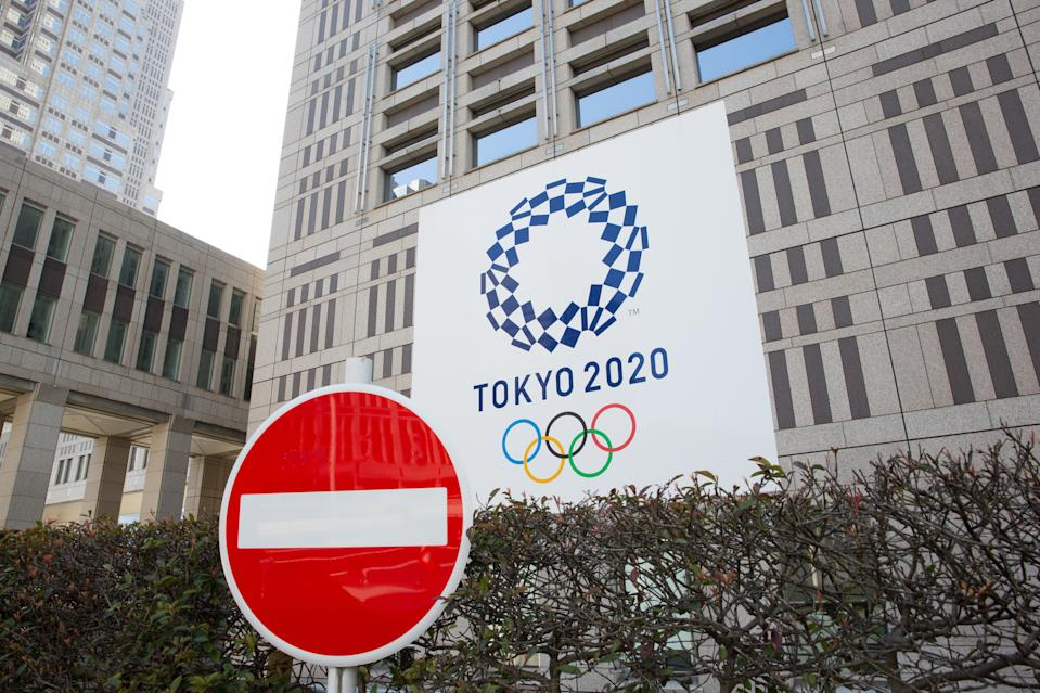 TOKYO, JAPAN - 2020/03/19: A stop sign in front of the Tokyo Metropolitan Government Building while the Tokyo 2020 Olympic Games banner is seen in the background.  Japanese start thinking that it would be the best to postpone the Tokyo 2020 Olympic and Paralympic Games due to the fear of spreading the Covid-19 Coronavirus more into its population. (Photo by Stanislav Kogiku/SOPA Images/LightRocket via Getty Images)