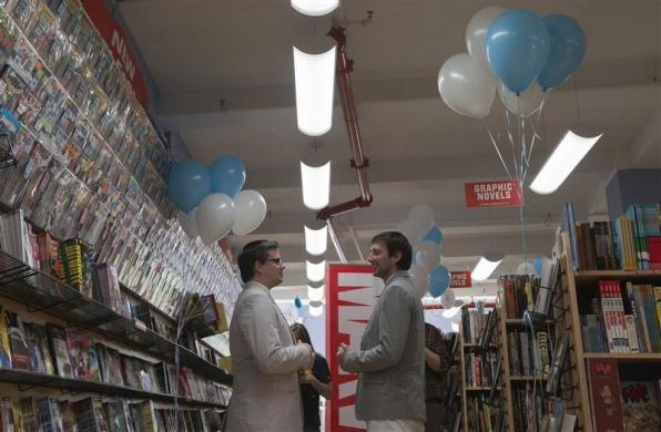 Scott Everhart (L) and Jason Welker stand amid comic books before their wedding ceremony in Manhattan, New York June 20, 2012. Midtown Comics delayed the opening of its downtown store for the wedding of Everhart, a healthcare site manager from Columbus, Ohio, and 33-year-old architect Welker. The real-life nuptials, complete with a band, balloons and decorations, coincided with the comic book union of Jean-Paul Beaubier, aka Northstar, who can move and fly at superhuman speed, and his long-term partner, Kyle, in the series Astonishing X-Men #51.