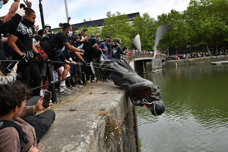 The statue is pushed in to the docks in Bristol (PA)