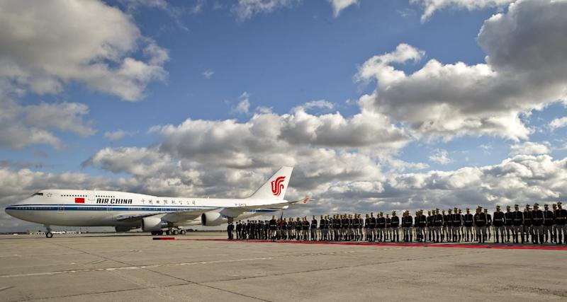 Honor guard soldiers stand as the airplane transporting China's Premier Li Keqiang parks on the runway of the Henri Coanda airport, outside Bucharest, Romania, Monday, Nov. 25, 2013. China's Premier will attend the China - Central and Eastern Europe meeting of heads of government, starting Tuesday in the Romanian capital.(AP Photo/Vadim Ghirda)