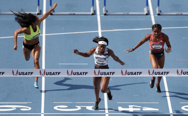 FILE - In this June 23, 2018, file photo, Keni Harrison, center, crosses the finish line ahead of Queen Harrison, left, and Christina Manning, right, to win the women's 100-meter hurdles final at the U.S. Championships athletics meet, in Des Moines, Iowa. Harrison will try to become just the second four-time meet champion in the 100-meter hurdles at this weekends Drake Relays. (AP Photo/Charlie Neibergall, File)