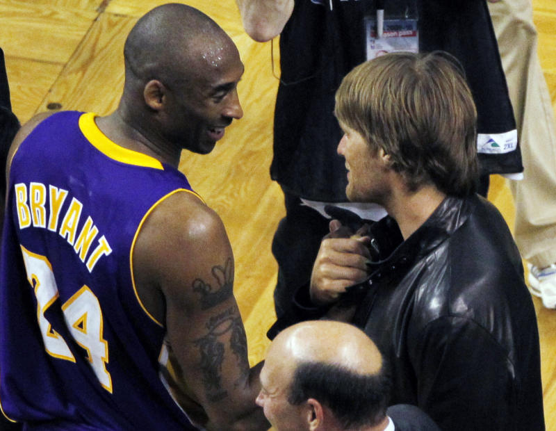 Los Angeles Lakers guard Kobe Bryant, left, talks to New England Patriots quarterback Tom Brady, right, after Game 3 of the NBA basketball finals between the Boston Celtics and the Lakers on Tuesday, June 8, 2010, in Boston. The Lakers won 91-84. (AP Photo/Charles Krupa)