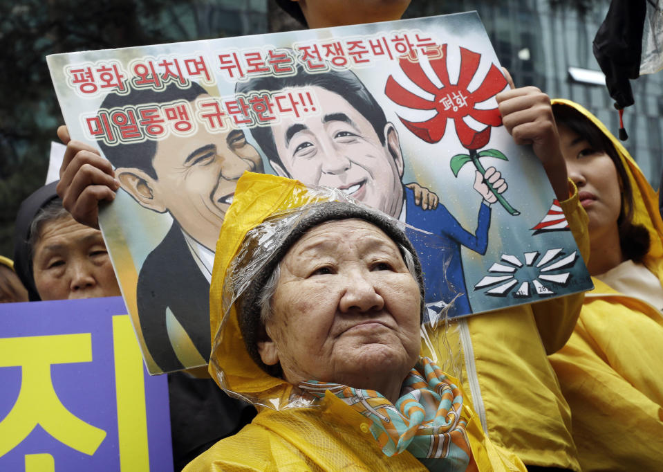 """Former comfort woman Kil Un-ock who was forced to serve for the Japanese troops as a sexual slave during World War II, attends a rally against a visit by Japanese Prime Minster Shinzo Abe to the United States, in front of the Japanese Embassy in Seoul, South Korea, Wednesday, April 29, 2015. Abe has sidestepped a question on whether he would apologize for the sexual enslavement of women by Japan's army during World War II. The letters at a card read """" Oppose the alliance between U.S. and Japan."""" (AP Photo/Ahn Young-joon)"""
