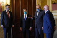 Senate Minority Leader Sen. Chuck Schumer of N.Y., second from right, talks with the newly elected senators, from left, Sen.-elect John Hickenlooper, D-Colo., Sen.-elect Ben Ray Lujan, D-N.M., and Sen.-elect Mark Kelly, D-Ariz., before a meeting on Capitol Hill in Washington, Monday, Nov. 9, 2020. (AP Photo/Susan Walsh)