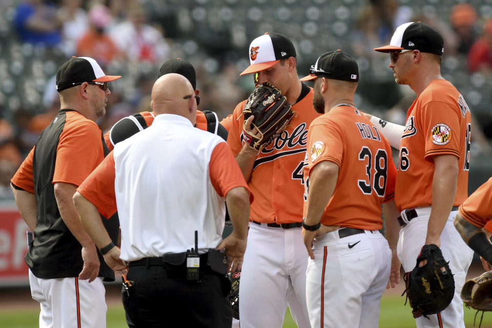 Baltimore Orioles starting pitcher John Means, center, speaks to a trainer before leaving the game with an apparent injury in the first inning of a baseball game against the Cleveland Indians, Saturday, June 5, 2021, in Baltimore. (AP Photo/Will Newton)