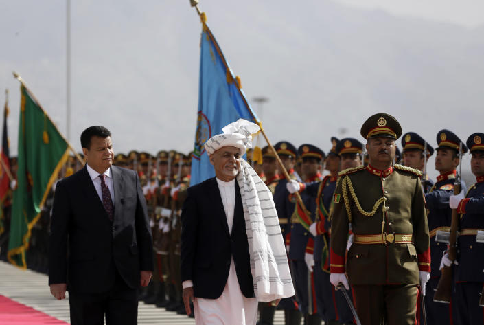 FILE - In this March 6, 2021 file photo, Afghan President Ashraf Ghani, center, inspects an honor guard during the opening ceremony of the new legislative session of the Parliament, in Kabul, Afghanistan. Afghanistan's embattled president left the country Sunday, Aug. 15, 2021, joining his fellow citizens and foreigners in a stampede fleeing the advancing Taliban and signaling the end of a 20-year Western experiment aimed at remaking Afghanistan. (AP Photo/Mariam Zuhaib, File)