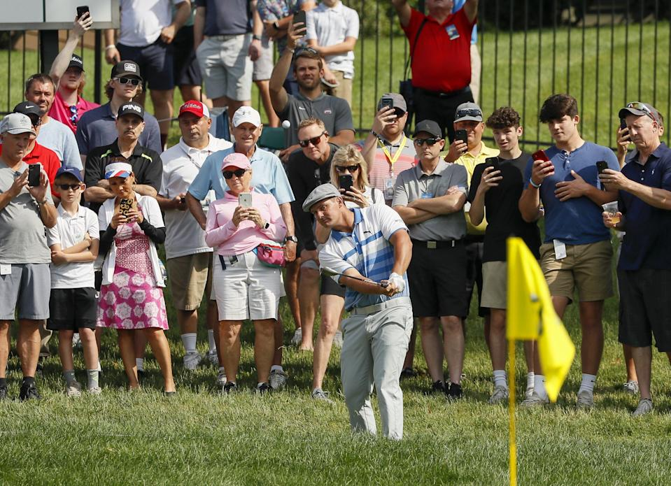 Fans watch as Bryson DeChambeau hits onto the 11th green at the Memorial on Friday.