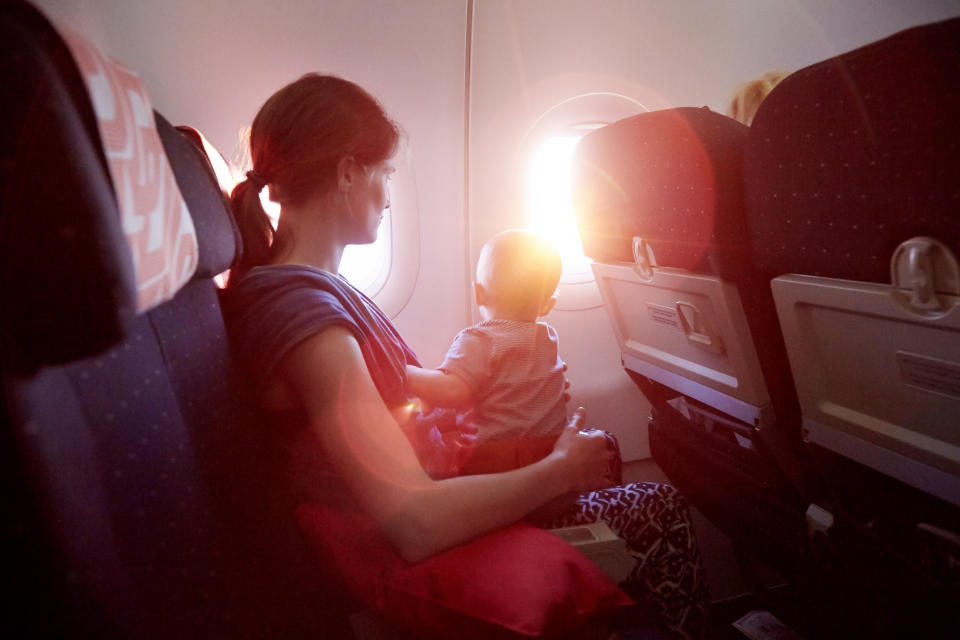 A photo of a mother and baby on airplane looking out of window.
