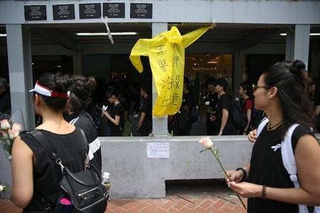 People pay respects at the site where a man fell from a scaffolding at the Pacific Place complex while protesting against a proposed extradition bill, near a raincoat similar to the one he wore, in Hong Kong