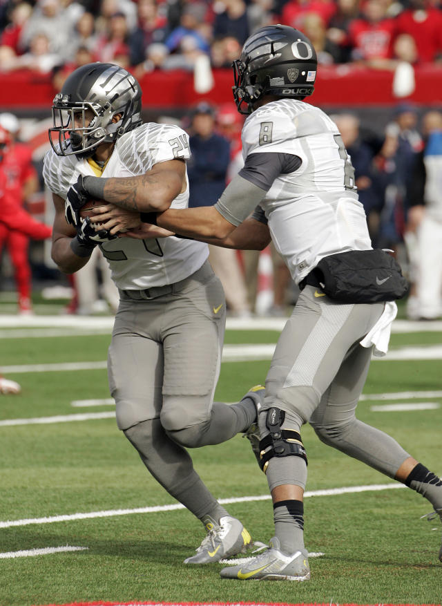 Oregon's starting quarterback Marcus Mariota (8) hands off the ball to Thomas Tyner (24) in the first half of an NCAA college football game against Arizona, Saturday, Nov. 23, 2013 in Tucson, Ariz. (AP Photo/Wily Low)