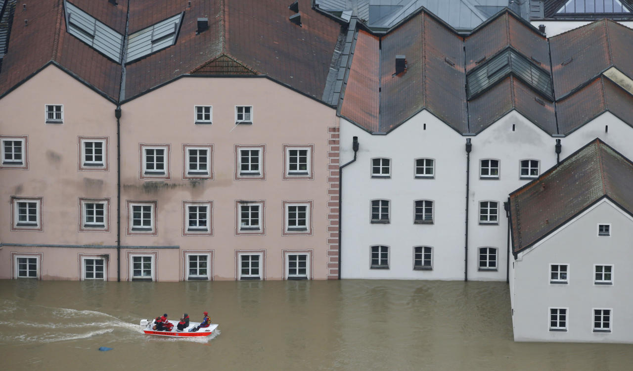 "Members of the Red Cross make their way by boats in the flooded street in the center of Passau, southern Germany, Monday, June 3, 2013. Raging waters from three rivers have flooded large parts of the southeast German city following days of heavy rainfall in central Europe. A spokesman for the city's crisis center said Monday that the situation was ""extremely dramatic"" and waters are expected to rise further by midday to their level highest in 70 years. (AP Photo/Matthias Schrader)"