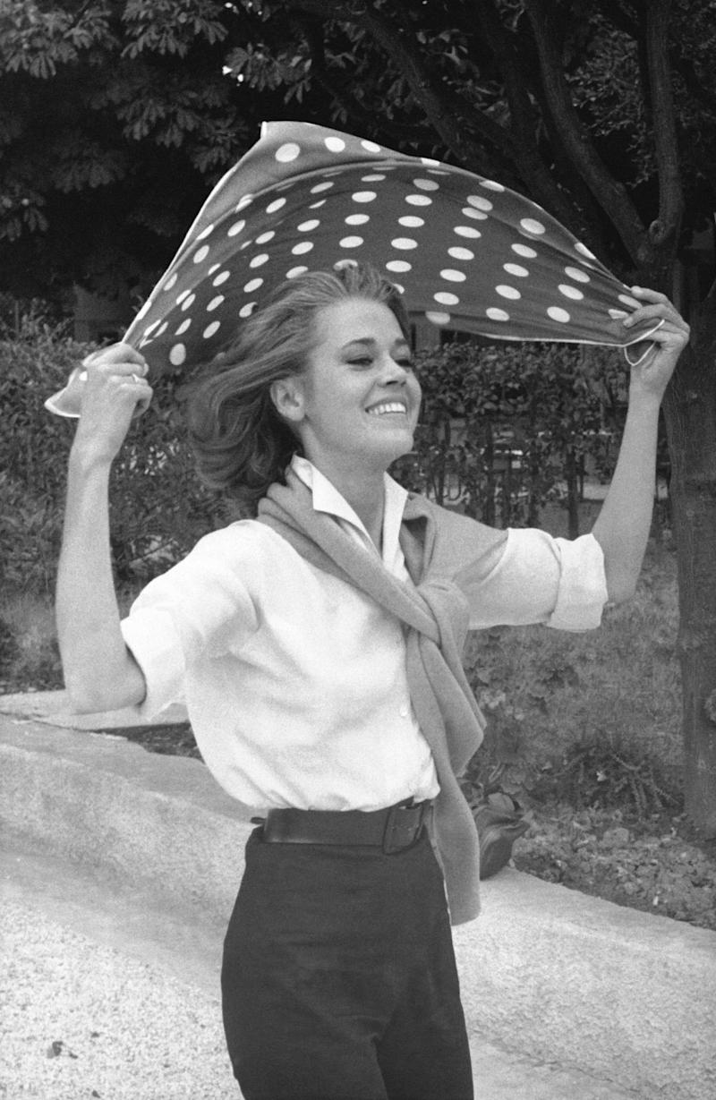 Fonda tries to tie a scarf around her head in this photo from 1964.