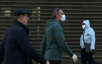 People wearing a mask against the spread of the new coronavirus walk during a curfew in downtown Belgrade, Serbia, Tuesday, April 21, 2020. Serbia's elderly on Tuesday ventured outside their homes for the first time in more than a month as the authorities eased some of the strict measures that have been in place against the new coronavirus. Serbia has introduced some of the toughest rules in Europe as part of efforts to curb the spread of the virus. (AP Photo/Darko Vojinovic)