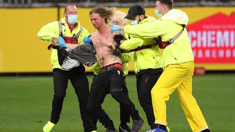 A pitch invader, pictured here being escorted from the field during Geelong's clash with Collingwood.