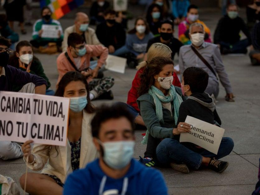 Youth environmental activists wear protective face masks and practice social distancing guidelines as one protester sits with a child and holds a placard reading 'Climate demand' during a protest in Madrid in September 2020 (Getty Images)