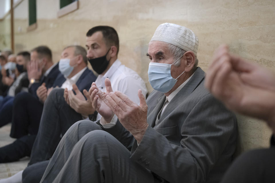 Bosnian Muslims, wearing face masks to protect themselves from the COVID-19 infection, attend Eid al-Fitr prayers in Konjic, Bosnia, Thursday, May 13, 2021. Muslims celebrated Eid al-Fitr in a subdued mood for a second year as the COVID-19 pandemic again forced mosque closings and family separations on the holiday marking the end of Ramadan. (AP Photo/Kemal Softic)