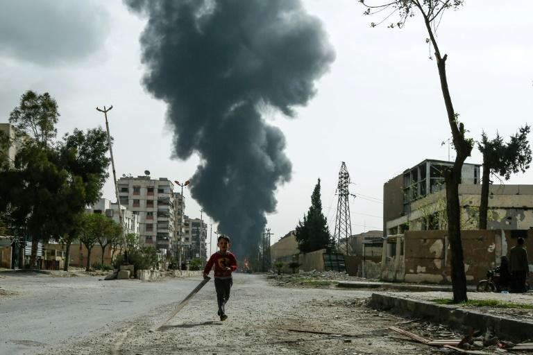 A child runs along a street in front of clouds of smoke following a reported air strike on Douma, the main town of Syria's rebel enclave of Eastern Ghouta, on March 20, 2018