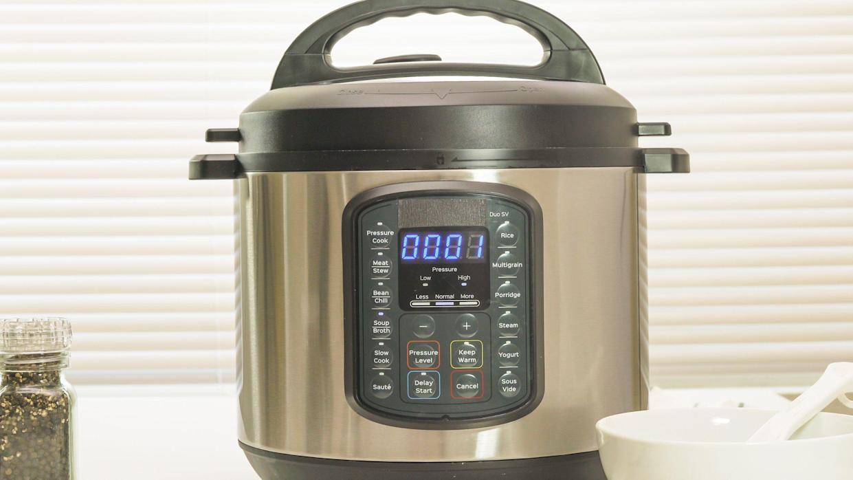 Modern electric multi cooker close up on kitchen table. Up to 1 minutes cooking time remaining