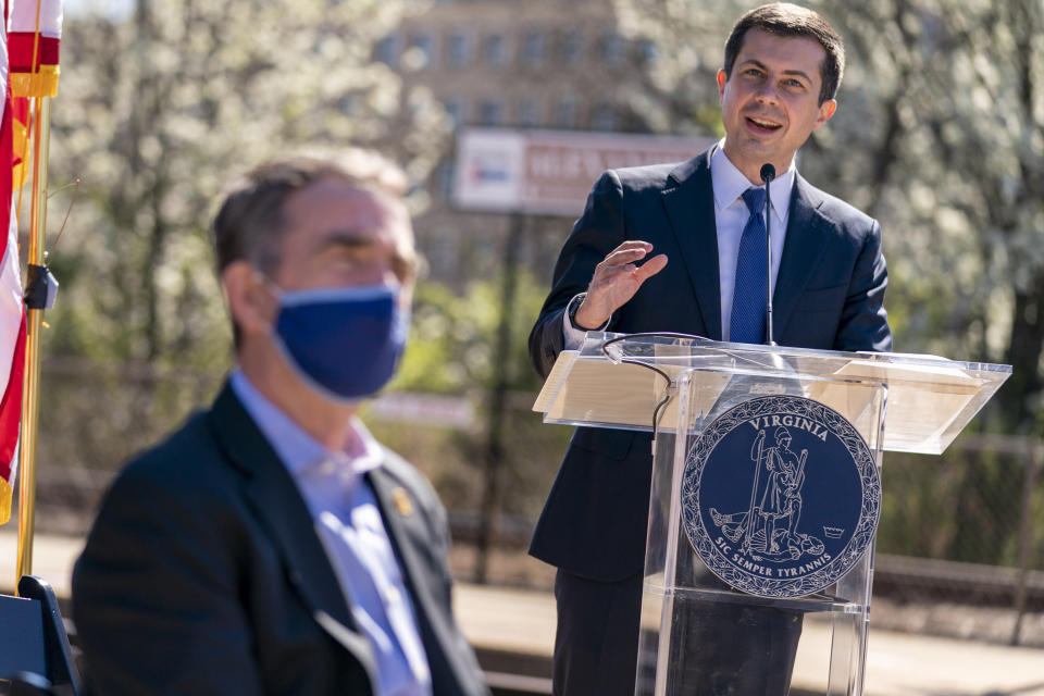 Transportation Secretary Pete Buttigieg, right, accompanied by and Virginia Gov. Ralph Northam, left, speaks at a news conference to announce the expansion of commuter rail in Virginia at the Amtrak and Virginia Railway Express (VRE) Alexandria Station, Tuesday, March 30, 2021, in Alexandria, Va. (AP Photo/Andrew Harnik)