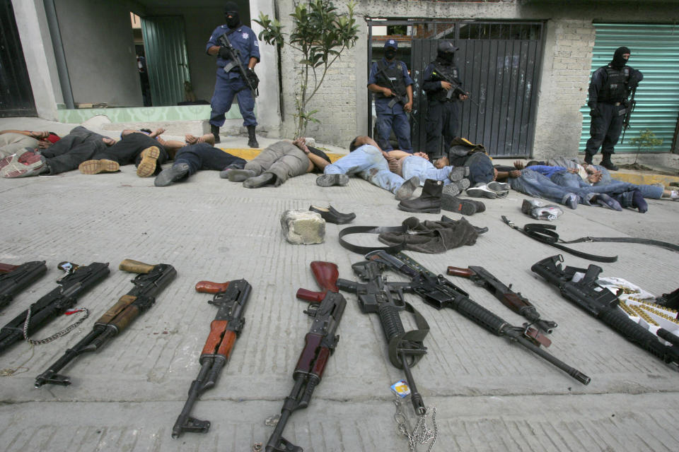 Federal policemen stand guard after a band of at least 18 men, suspected by police to be kidnappers, were captured with automatic weapons during a shootout with the police in Villa Nicolas Romero state of Mexico, September 2, 2008. Two of the suspected kidnappers and one federal police officer died in the shootout, according to the police.   REUTERS/Juan Garcia (MEXICO)