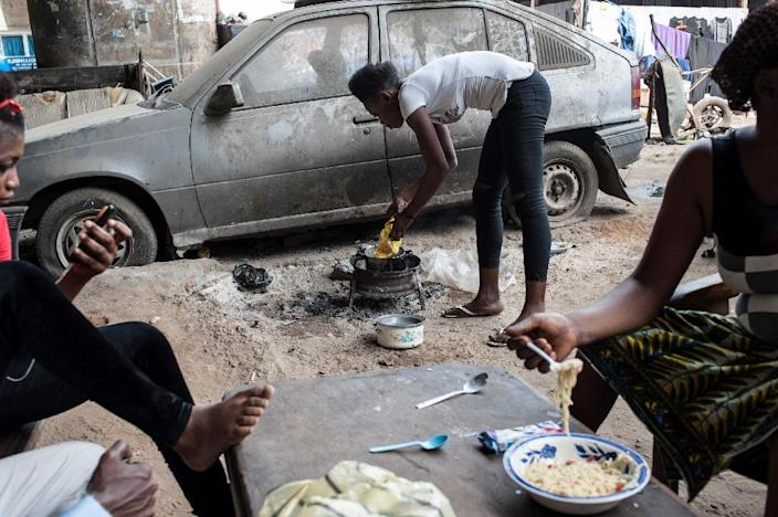 """Women cook food under a bridge in Lagos as 70 percent of Nigerians live in poverty, a theme of rapper Falz's """"This is Nigeria"""" (AFP Photo/STEFAN HEUNIS)"""