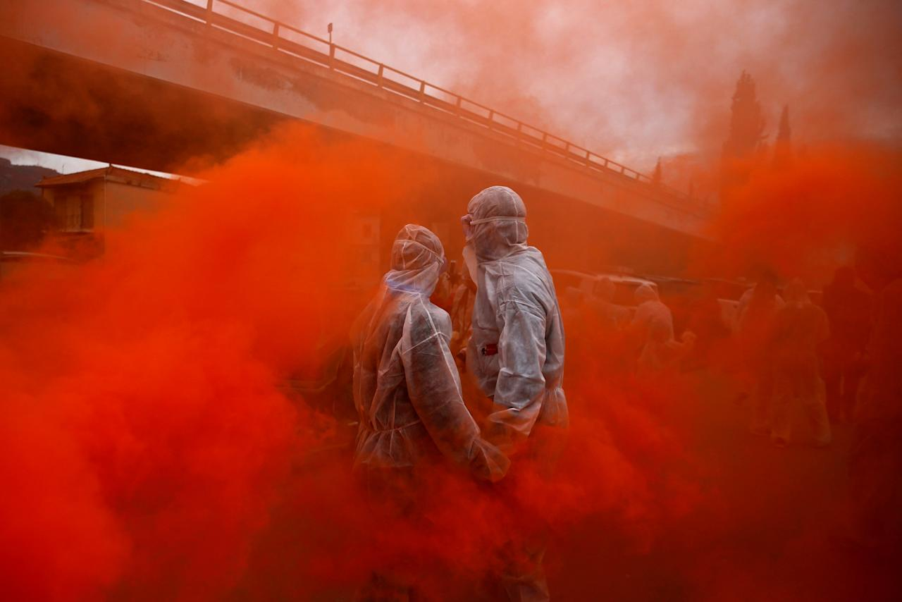 """Two revellers are seen amid flare smoke as they celebrate """"Ash Monday"""" by participating in a colourful """"flour war"""", a traditional festivity marking the end of the carnival season and the start of the 40-day Lent period until the Orthodox Easter, in the port town of Galaxidi, Greece February 19, 2018. REUTERS/Alkis Konstantinidis     TPX IMAGES OF THE DAY"""