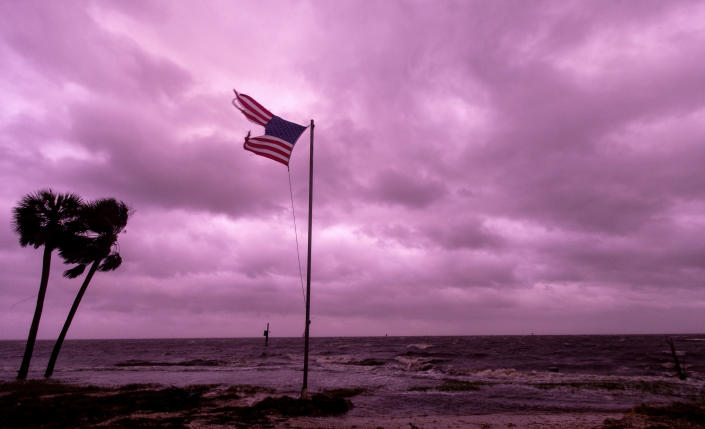<p>An American flag battered by Hurricane Michael continues to fly in the in the rose colored light of sunset at Shell Point Beach on October 10, 2018 in Crawfordville, Florida.The hurricane hit the Florida Panhandle as a category 4 storm. (Photo by Mark Wallheiser/Getty Images) </p>