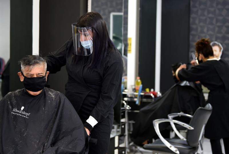 A client gets a haircut at a beauty salon, during the COVID-19 pandemic, in Mexico City on June 29, 2020. - Starting this week Mexico City is allowing the reopening of shops, street markets and athletic complexes but with limited capacity and hours. Hotels and restaurants in the capital will reopen at about 30% seating capacity. (Photo by ALFREDO ESTRELLA / AFP) (Photo by ALFREDO ESTRELLA/AFP via Getty Images)
