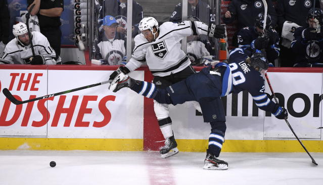 Winnipeg Jets' Patrik Laine (29) checks Los Angeles Kings' Alex Iafallo (19) during the third period of an NHL hockey game Tuesday, Oct. 22, 2019, in Winnipeg, Manitoba. (Fred Greenslade/The Canadian Press via AP)