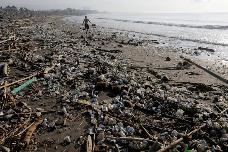 A local resident walks along a section of Matahari Terbit beach covered in plastic and other debris washed ashore by seasonal winds near Sanur, Bali, Indonesia. (Photo: Johannes Christo/Reuters)