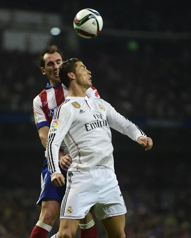 Real Madrid's Portuguese forward Cristiano Ronaldo (R) vies with Atletico Madrid's Uruguayan defender Diego Godin during their Spanish Copa del Rey round of 16 second leg football match in Madrid on January 15, 2015 (AFP Photo/Pierre-Philippe Marcou)